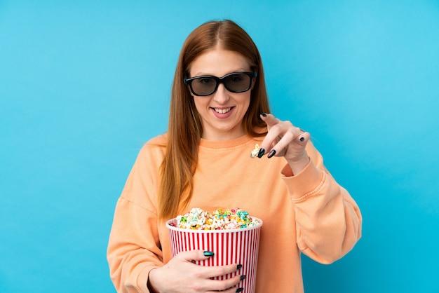 Молодая рыжая женщина над изолированной стеной с 3d-очками и держит большое ведро попкорнов, указывая вперед