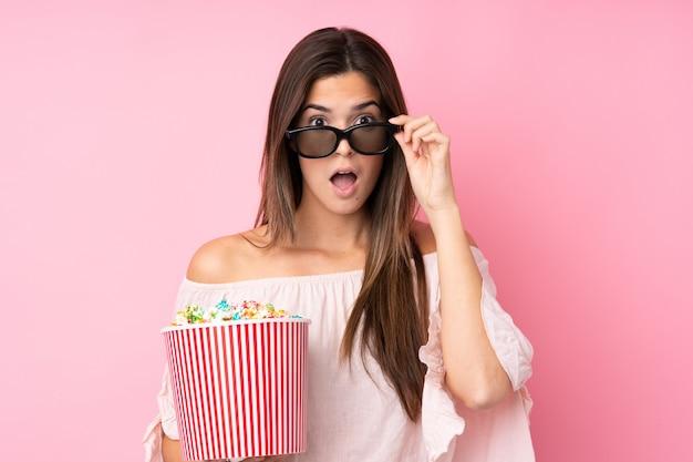 Девушка-подросток над изолированной розовой стеной, удивленная очками 3d и держащая большое ведро попкорна