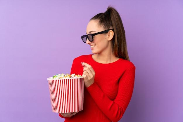 Молодая брюнетка женщина над изолированных фиолетовые стены с 3d-очки и проведение большое ведро попкорна