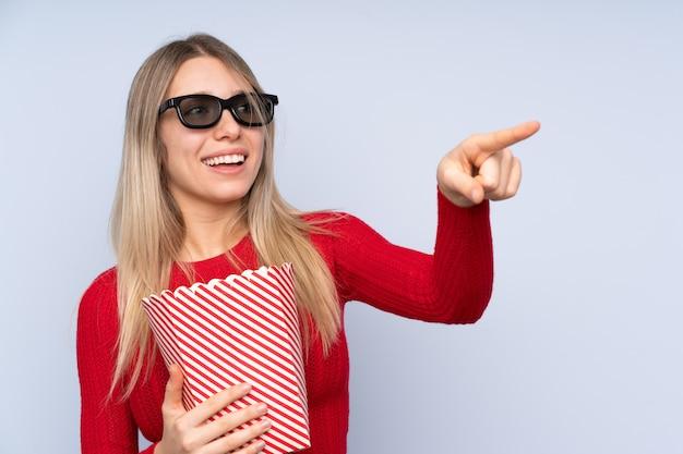 Молодая белокурая женщина над изолированной синей стеной с 3d-очками и держащей большое ведро попкорнов, указывая в сторону