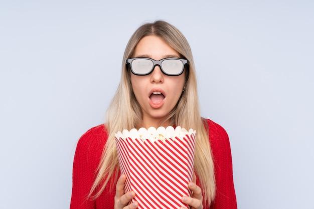 Молодая блондинка удивилась с очками 3d и держала в руках большое ведро попкорна