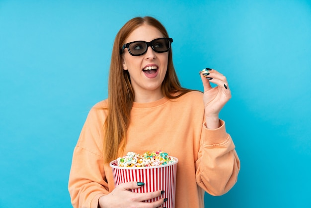 Рыжая молодая женщина с очками 3d держит большое ведро попкорна