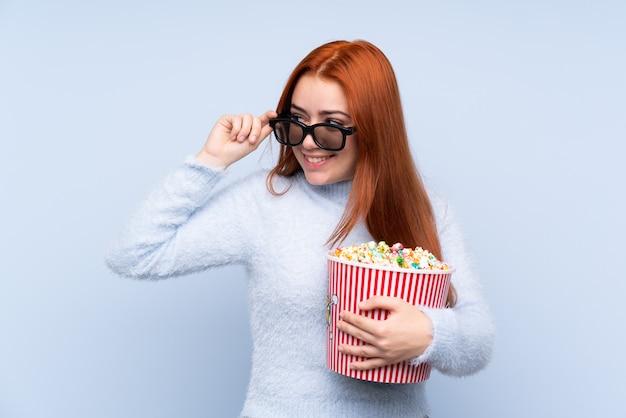 Рыжий подросток женщина с 3d-очки и держит большое ведро попкорна