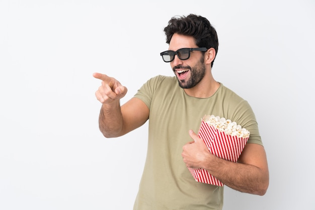 Молодой красивый мужчина с бородой над изолированной белой стеной с 3d-очками и держит большое ведро попкорна, указывая вперед