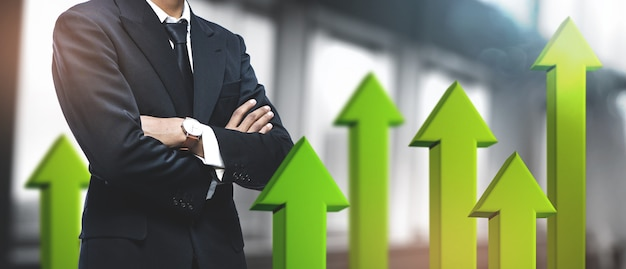 肯定的な成長ビジネスの成功。ぼやけたオフィスのアジア系のビジネスマン。 3d緑矢印