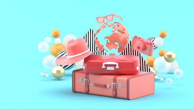 カメラとハットオンブルーに囲まれた地球儀の下のスーツケース。 3dレンダリング。