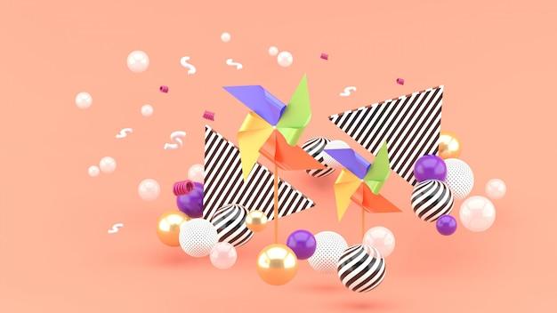 ピンクのカラフルなボールに囲まれた色とりどりの紙タービン。 3dレンダリング。