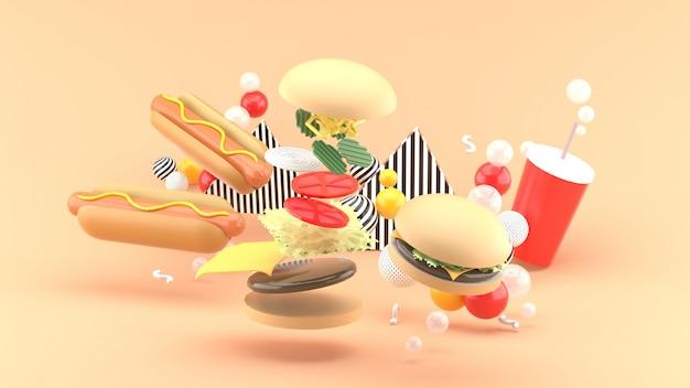 Гамбургеры, хот-доги и безалкогольные напитки среди разноцветных шариков на оранжевом. 3d-рендеринг.