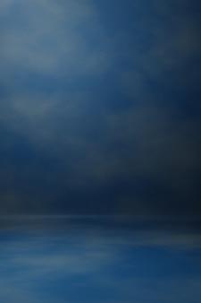 写真スタジオの肖像画の背景。背景には、スクラッチテクスチャダークブルー、スポットライトと雲の空が描かれています。 3dレンダリング