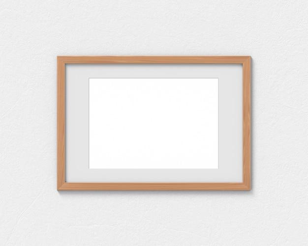 壁に掛かっている境界線を持つ水平木製フレームモックアップ。画像またはテキストの空のベース。 3dレンダリング。