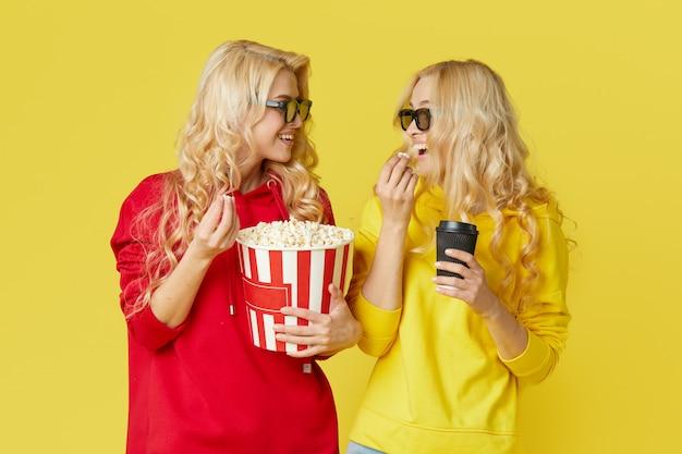 Шокированные молодые модели женщин в 3d очках едят попкорн, смотрится страшно кино. изолированный на желтой стене