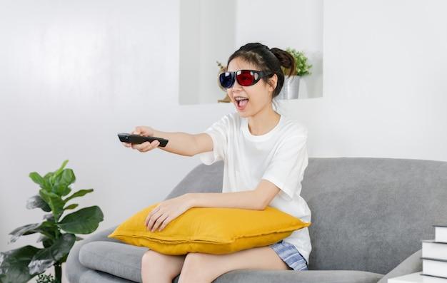 若いアジアの女性は、家のソファーに座ってテレビのリモコンを押しながら3dメガネをかけてリラックスした日に映画を鑑賞します。