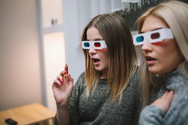 映画を見ている3dメガネの衝撃を受けた女性