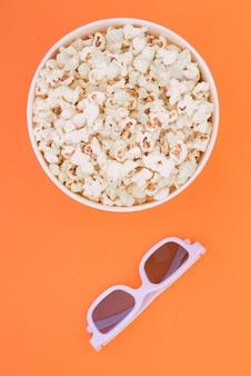 Бумажный стаканчик с попкорном и 3d очки на оранжевом фоне, вид сверху. квартира лежала.