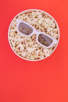 Стекла 3d лежат на чашке при попкорн изолированный на красной предпосылке. концепция кино.
