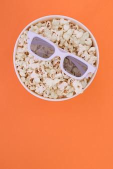 Очки 3d лежат на чашке при попкорн изолированный на оранжевой предпосылке. концепция кино.
