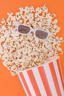 Попкорн льется из бумажной миски на оранжевый фон, а 3d очки для просмотра фильма, вид сверху