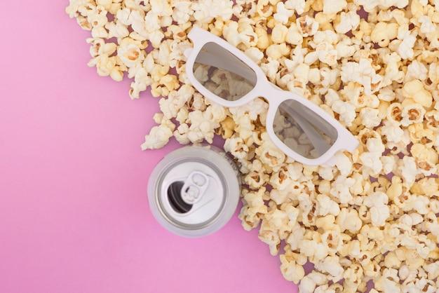 Белые 3d очки, металлическая банка с напитком, бумажный стаканчик и свежий сырный попкорн на пастельно-розовом фоне