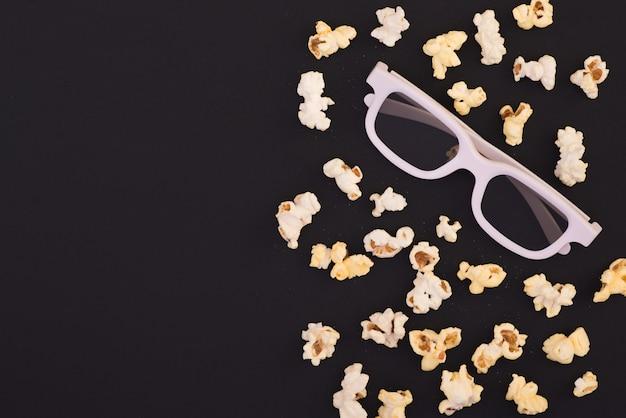 Попкорн и белые 3d очки на ярком темном фоне, вид сверху. фон. шаблон.