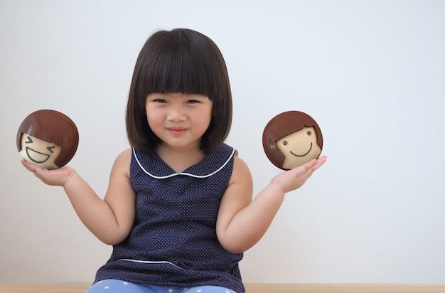 幸せなアジアの子供の女の子が遊んでいます。球体玩具の写真と3dレンダリングの組み合わせ。