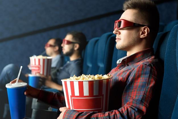 Его пугающий день. красивый расслабленный мужчина в 3d очках смотрит фильмы с попкорном и напитками