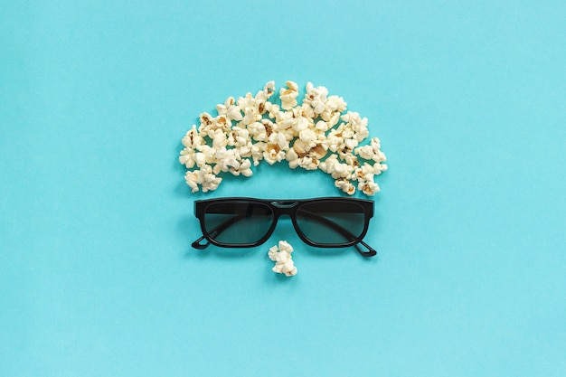 Абстрактный образ зрителя, 3d-очки и попкорн на синем фоне.