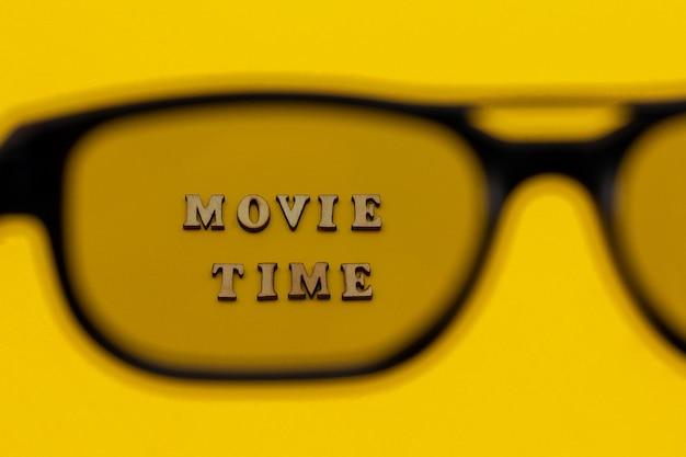 黄色い紙の背景に3dメガネを通してテキスト映画の時間に焦点を当てます。