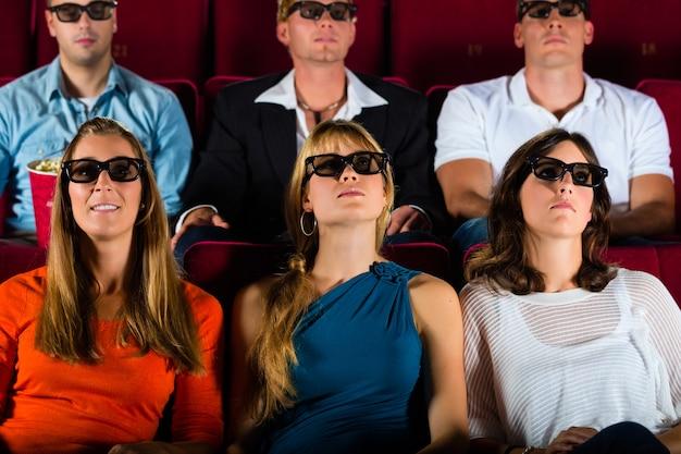 Молодые люди напряженно смотрят 3d фильм в кинотеатре