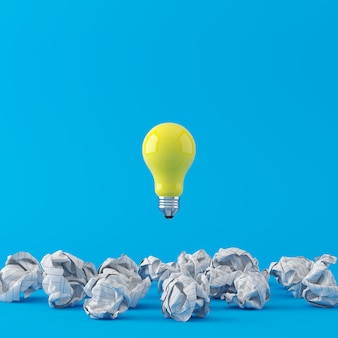 最小限の概念青い背景に白のしわくちゃの紙に浮かぶ優れた黄色の電球。 3dレンダリング