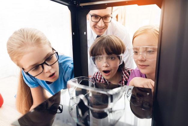 子供たちは先生と一緒に3dプリンターでさまざまなアイテムを印刷します。