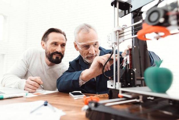 Два инженера печатают детали на 3d принтере.