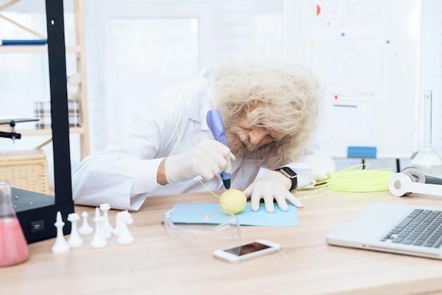 Ученый с седой бородой рисует зеленое яблоко с 3d ручкой.
