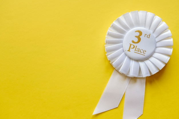 3rd place white ribbon rosette on yellow