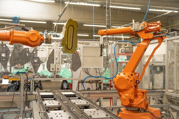 Роботизированный автоматический манипулятор на заводе для точного производства и объединения отдельных частей в единое целое. роботизация производства. промышленность 4.0