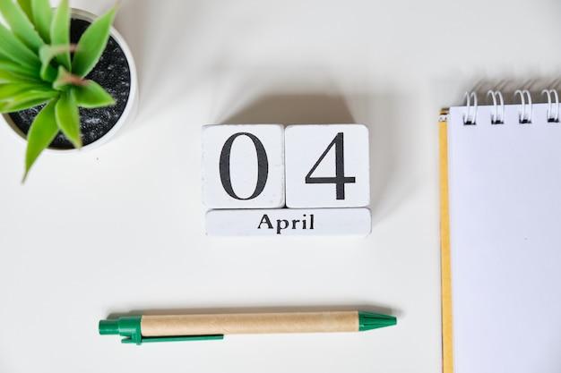 白い木製の立方体の日付-4月1日、4月4日、白いテーブル。上面図。
