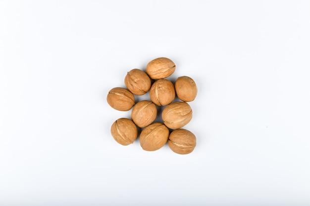 Грецкие орехи на белом. крупным планом вид грецких орехов. в грецких орехах 4 воды, 15 белков, 65 жиров и 14 углеводов, в том числе 7 пищевых волокон. в эталонной порции 100 грамм.