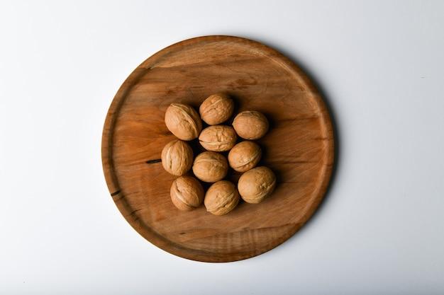 木製の道具にクルミ。クルミのビューを閉じます。クルミは、4つの水、15のタンパク質、65の脂肪、7つの食物繊維を含む14の炭水化物です。 100グラムの参照部分で。