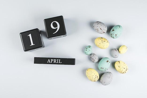 灰色の背景にイースターカレンダー4月19日。春のイースターホリデーカード。パステルカラーのイースターエッグ。上面図。フラットレイ