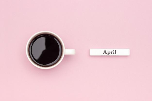 木製カレンダー春4月とパステルピンクの紙の背景にブラックコーヒー1杯