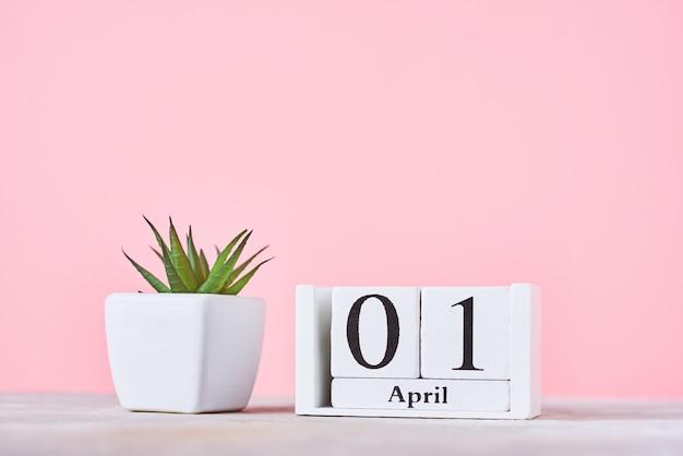 木製ブロックカレンダー4月1日の日付とピンクの背景の植物。エイプリルフールのコンセプト