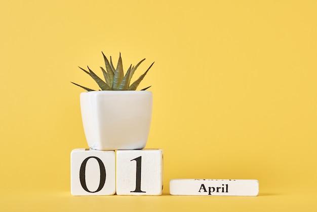 木製ブロックカレンダー4月1日の日付と黄色の背景の植物。エイプリルフールのコンセプト