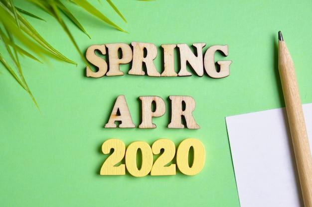 春の概念-新しい年の4月。手紙と鉛筆で紙のシートを持つ木製の番号2020
