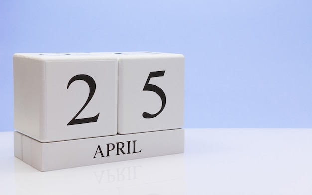 4月25日月の25日目、反射と白いテーブルに毎日のカレンダー