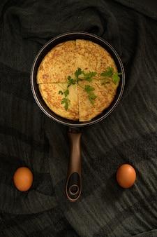ロースターの4つの部分と側面に2つの卵に分かれたオムレツの垂直ショット