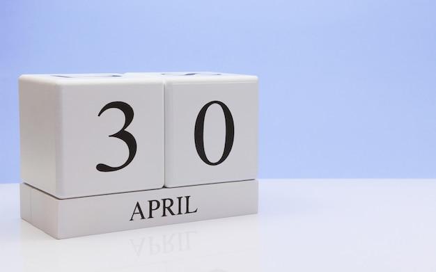 4月30日30日、反射と白いテーブルの上の毎日のカレンダー