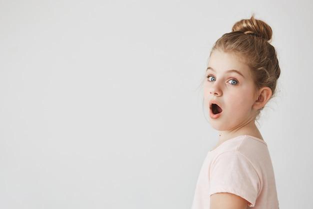 映画の大人のシーンでショックを受けて口を開けて眉毛を上げ、4分の3でポーズをとるお団子髪型の金髪少女のクローズアップ。