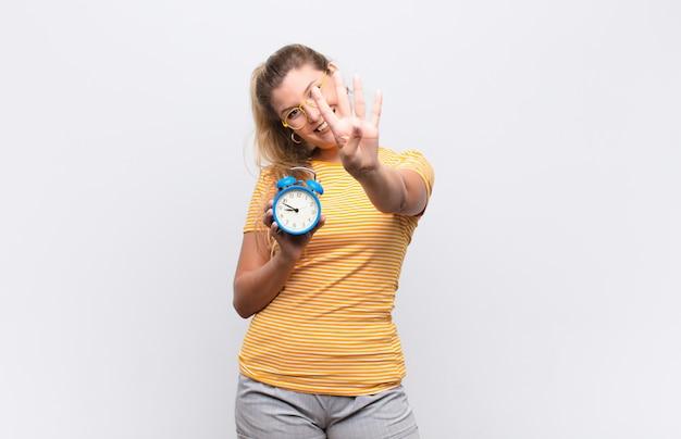 目覚まし時計でカウントダウン、笑顔でフレンドリーな若いかなりラテン女性、手で前方に4または4番目を示す