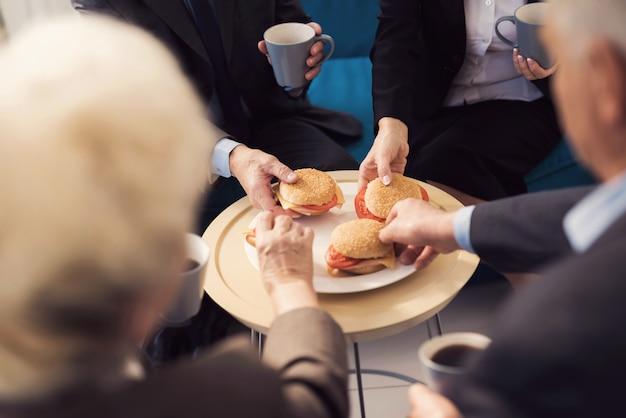 皿の上の4つのハンバーガーと4つの手のクローズアップ写真。