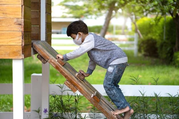 Азиатский мальчик 4-5 лет поднимается по лестнице на детской площадке.