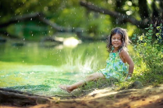 緑のドレスを着て、森の川の背景に裸足で4〜5歳の女の子